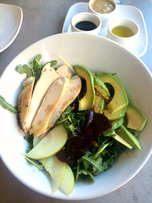 Whole30 compliant salad with arugula, apple, beets, chicken, avocado and pumpkin seeds.