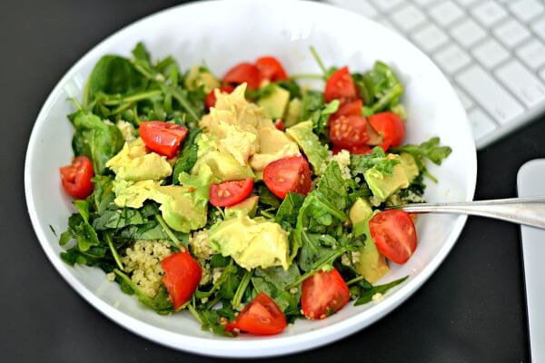 Salad with arugula, spinach, quinoa, tomatoes, avocado, hummus.