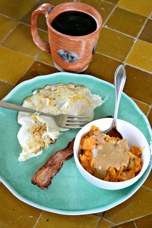 Mashed sweet potatoes and bananas with coconut milk and topped with cashew butter, a slice of bacon and two fried eggs