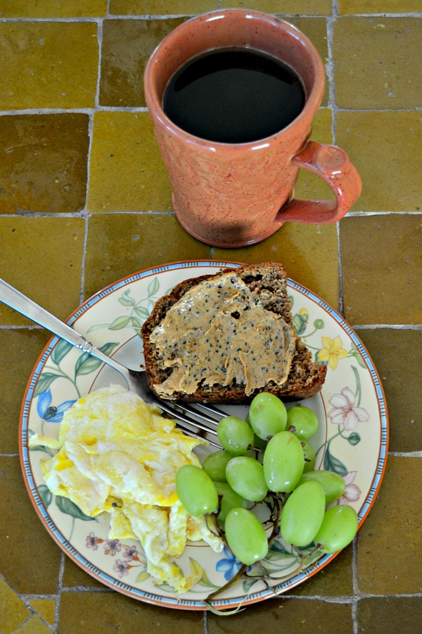 Coconut peanut butter banana bread topped with cardamom chia cashew butter along with two scrambled eggs and grapes
