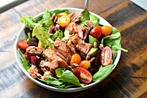 Greens, leftover sriracha lime salmon, roasted beets, tomatoes, pecans, avocado, cucumbers, dried cranberries.
