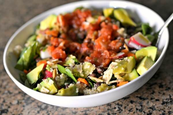 chopped spinach with quinoa, avocado, black beans, carrots, radishes and crushed tortilla chips with avocado vinaigrette and salsa