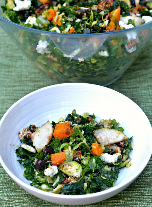 Shredded brussels sprout and kale salad features roasted butternut squash, sliced pears, toasted pecans and honey goat cheese topped with a chopped date and balsamic vinaigrette.