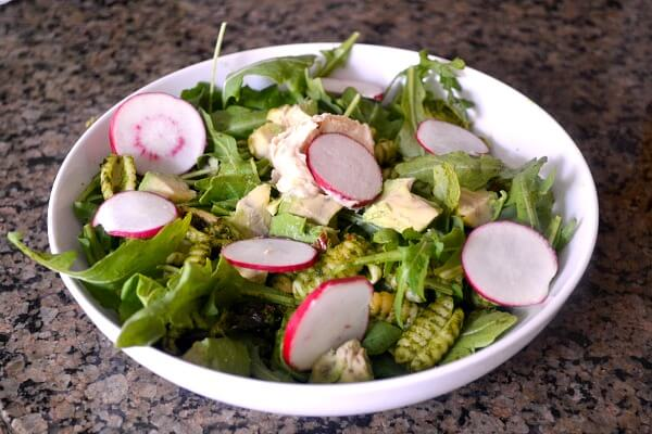 leftover kale pesto pasta tossed with arugula and topped with radishes, avocado and hummus