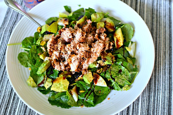 Salad with baby kale, avocado, pears, pistachios and a can of pink salmon.
