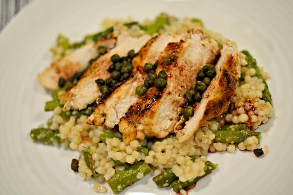 Seared chicken over pearled couscous with asparagus, crispy capers and a blood orange sauce.