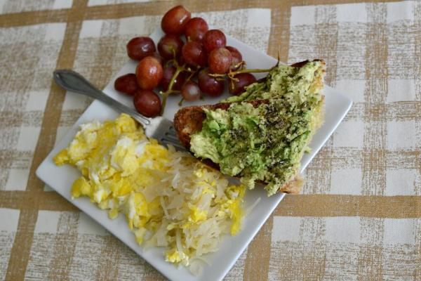 Avocaodo toast on sourdough with scrambled eggs, sauerkraut and grapes.