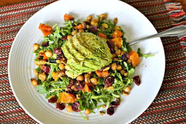 Arugula tossed with tahini turmeric dressing and topped with roasted butternut squash, pan-roasted spiced chickpeas, pistachios, dried cranberries, half an avocaodo and Be Run Curry Seed Salt.