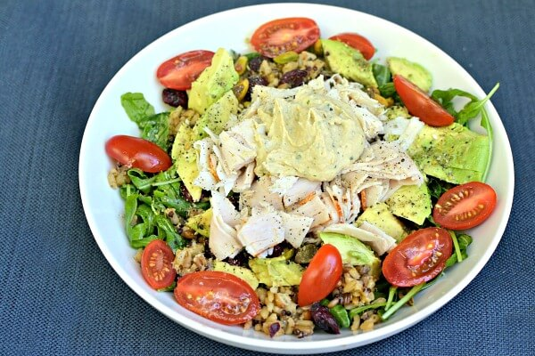 Arugula dressed with olive oil and lemon juice then topped with a grain blend, avocado, dried cranberries, turkey, pistachios, tomatoes and hummus