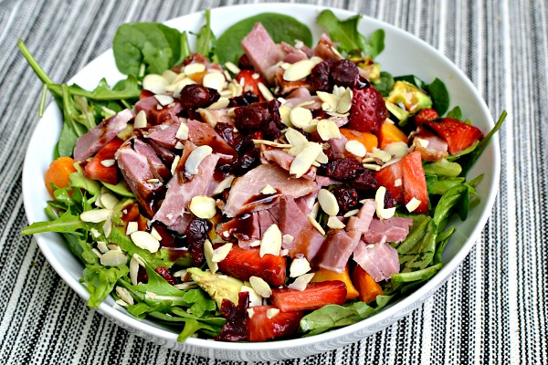 Salad with arugula, spinach, ham, dried cranberries, sliced almonds, avocado, butternut squash and strawberries.