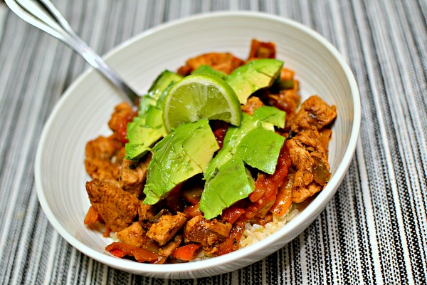 leftover chicken tostada topping over brown rice with salsa, avocado and a squeeze of lime