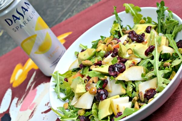 Salad with arugula, pears, avocado, pistachios, dried cranberries and a sesame ginger dressing
