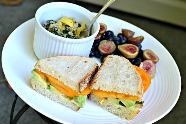tomato and avocado sandwich on sourdough with mayo and basil. Kale and quinoa salad, blueberries and figs on the side.