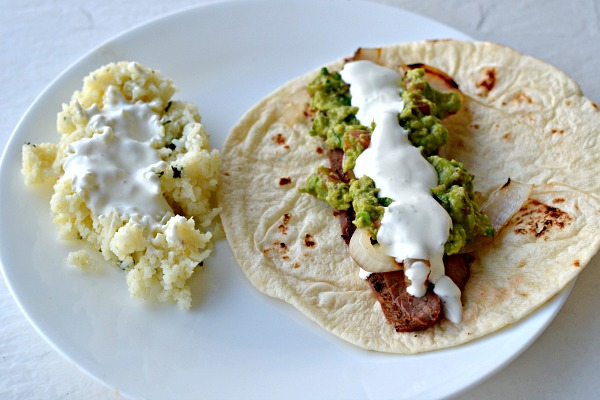 Flank steak fajitas with grilled onions, guacamole and lime crema. Cliantro-lime rice on the side.