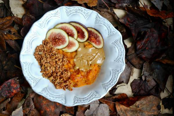 Fall sweet potato breakfast bowl topped with granola, sunflower seed butter and figs