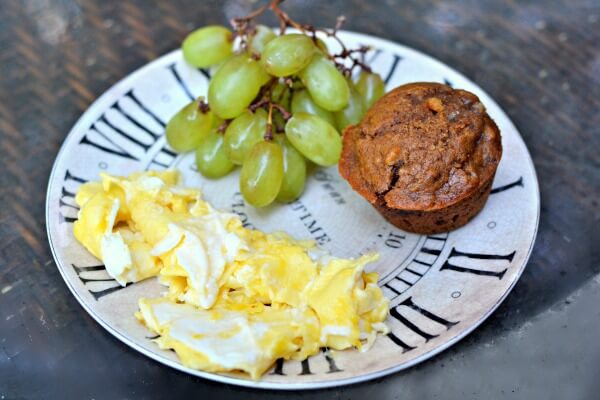 Two eggs scrambled in Kerrygold butter, a pumpkin muffin and grapes.