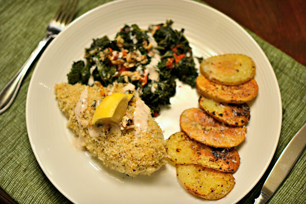 Panko crusted caesar chicken with roasted kale and tomatoes and roasted potatoes.