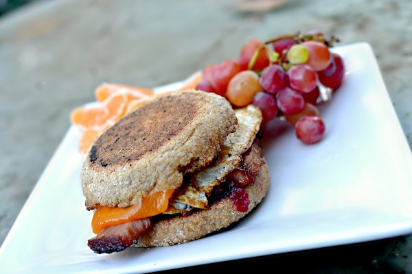 """Cranberry sauce, ham, a fried egg and cheddar cheese on a buttered whole wheat """"British"""" muffin."""