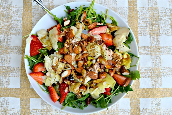 Salad with arugula, strawberries, artichokes, toasted nuts, dried cranberries and avocado with homemade dijon honey balsamic dressing.