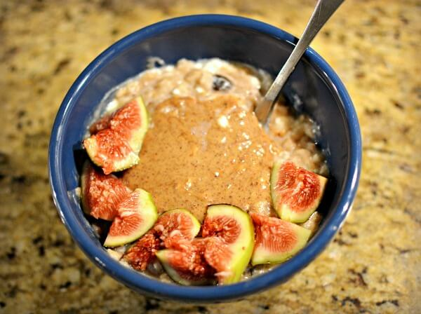 banana oatmeal with cottage cheese stirred in and topped with almond butter and figs
