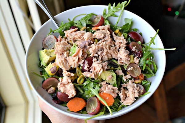 arugula tossed in a miso dressing and topped with avocado, carrots, grapes, pistachios, hemp seeds and canned salmon