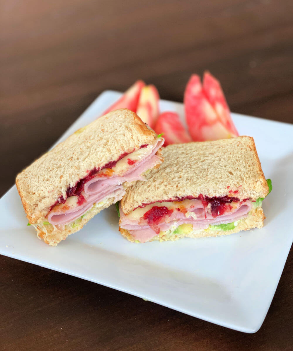ham sandwich with melted white cheddar, cranberry sauce and avocado