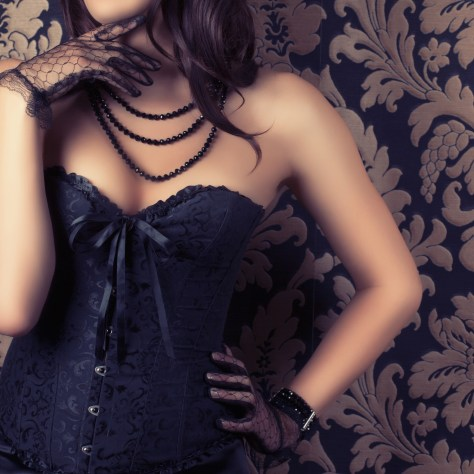 woman wearing corset and black pearl necklace
