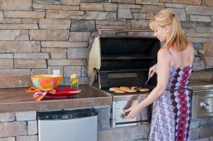Picture of Attractive blond caucasian woman using a gas barbeque grill in an outdoor kitchen