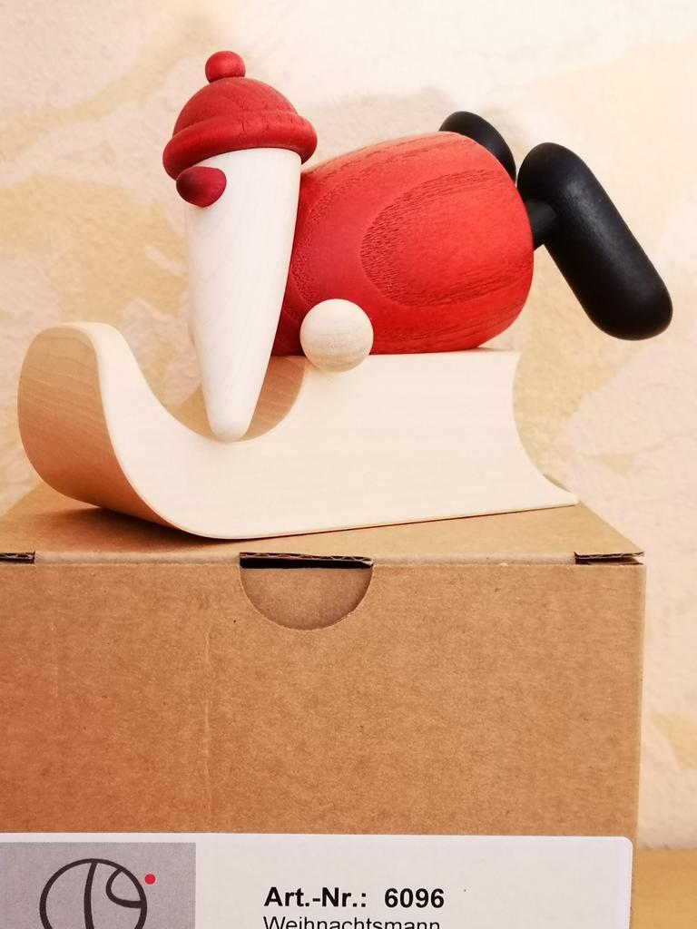 Weihnachtsmann auf Schlitten liegend