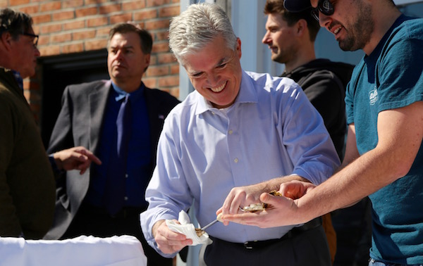 Suffolk County Executive Steve Bellone tries his hand at shucking oysters at the March 11 press conference at Catch Oyster Bar in Patchogue.