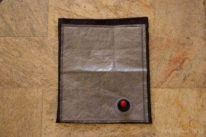 Cortar o tecido 2 a 4 cm maior para todos os lados em relação ao tamanho da bolsa plástica. Aproveite o posicionamento da bolsa de vinho para marcar onde deverá ficar posicionado o orifício que dará espaço para a torneira.