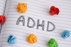 adhd written on notebook paper with crumpled colorful papers on top