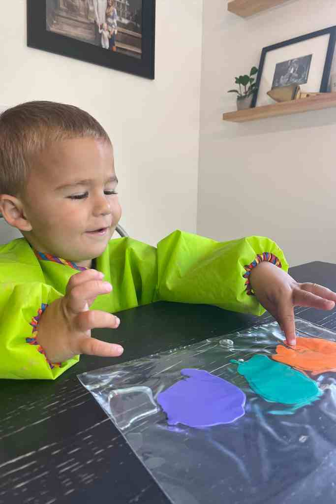 Toddler mixing paint in bag