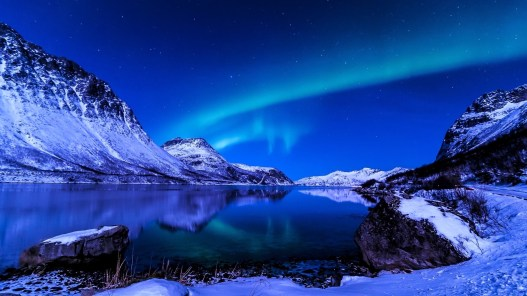 nice place here where is this high and white mountain and the sky is full of green Aurora borealis .