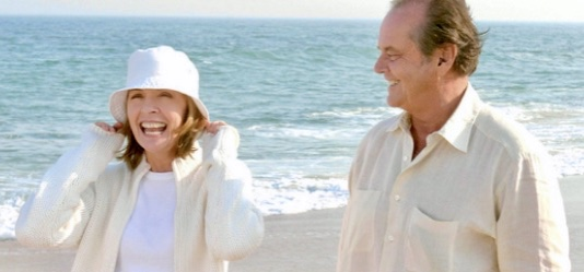 Man and woman walking on the beach smiling, waves in background