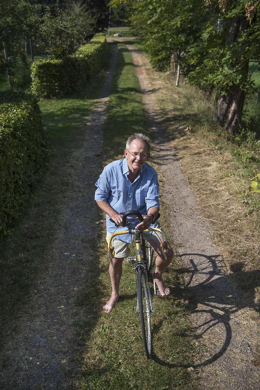 Jan Wittenberg em sua bicicleta em rua sem calçamento.