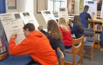 Student athletes sign their athletic letters in the HS library.