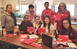 Penn Manor HS ELL students display their cards. They are, (sitting, from left) Alisa Johnson, Chelyann Perez-Irizarry, Cece Fernandez, Sol Sanchez (standing, from left)  Edna Almanza, Wah Wah, Anup Tamang and Douaa Jellouf.