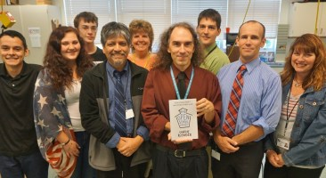 Penn Manor technology staff members and student apprentices pose with the new book.