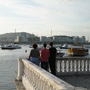 Na imagem, integrantes da plataforma online Barkus aparcem de costas. Ao fundo se vê parte da Guanabara, no Rio