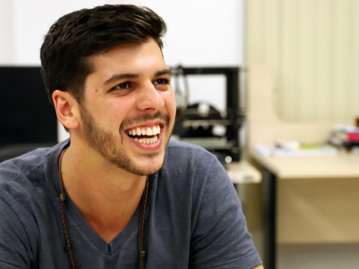 Victor Hazin, que sorri, tem cabelos curtos e sua camiseta cinza, decidiu unir a neurociência e a tecnologia em prol da recuperação de pessoas que sofreram AVC
