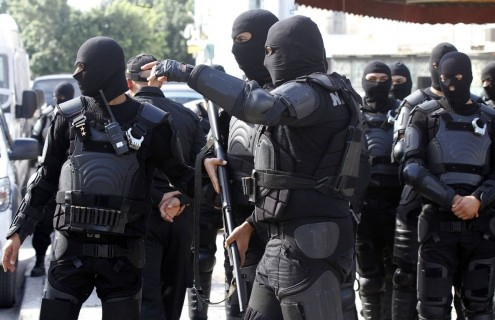 Riot police stand guard after Friday prayers near the al-Fatah mosque in Tunis