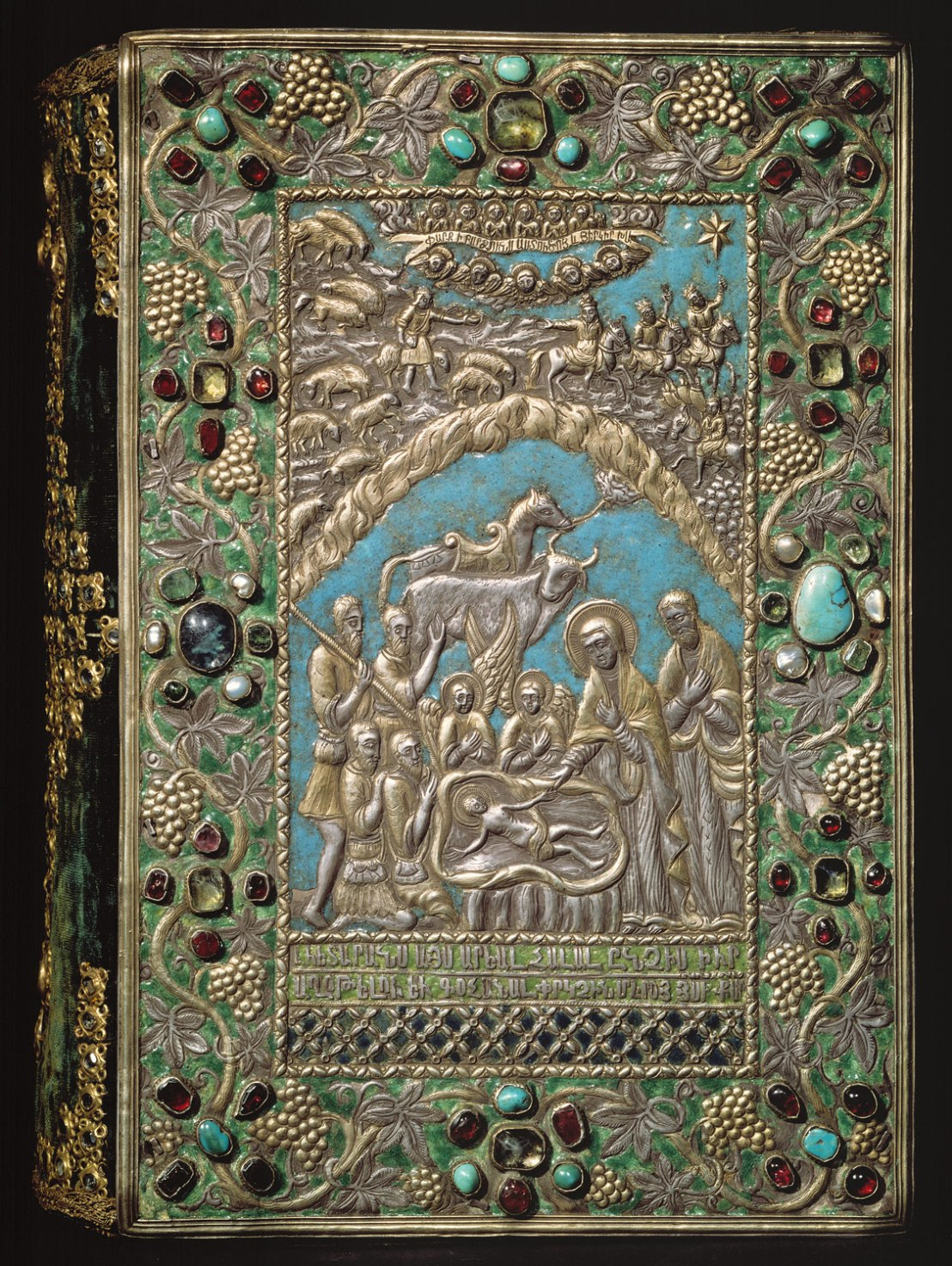 "This jeweled, enameled, and gilt-silver repoussé cover for a 13th century Armenian gospel is an examples of the work produced in the late seventeenth-century silversmith workshop of Kayseri. Both front and back cover are signed, informing us that they were made in Kayseri in 1691 by Astuatsatur Shahamir. The central image on the front cover depicts the Adoration of the Shepherds, and above, the magi following the star. Amid angels, the banner in the sky proclaims, ""Glory to God in the highest and on Earth peace."" The cover was attached to a gospel copied and illuminated by a thirteenth-century scribe named Grigor, from Cilicia."