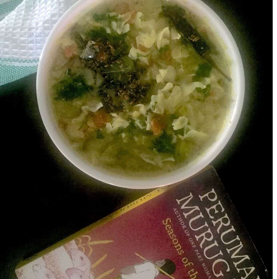 Green cabbage kootu/ stew with lentils and coconut paste, in a white bowl, garnished with coriander leaves. A red and black book by a Tamil author in the foreground, all on a black backgroundand a white and green napkin at the back.