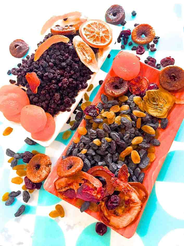 A variety of dry fruits to soak fruit for Christmas cake, on an orange plate with a blue and white backgroun
