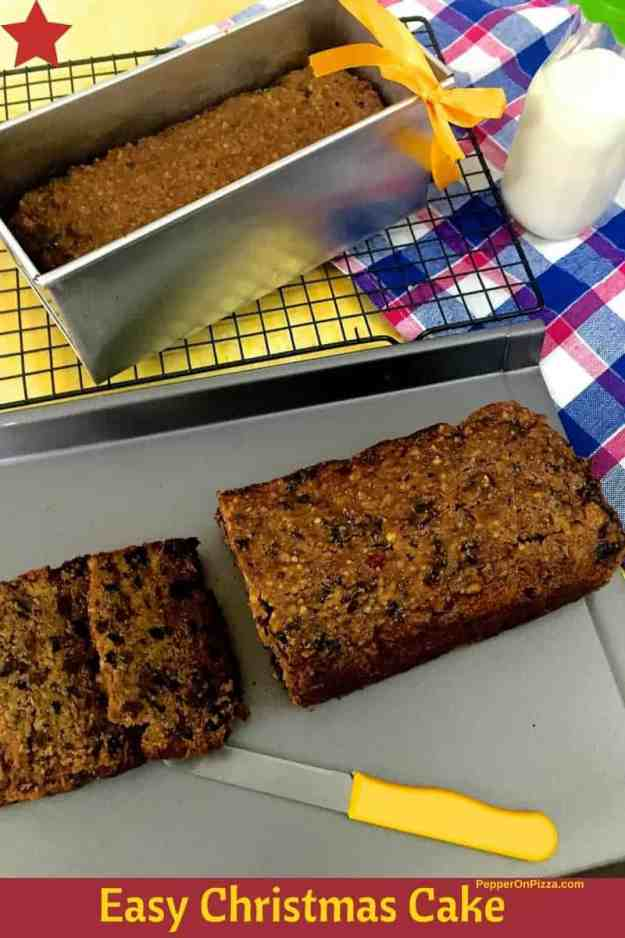 Christmas Fruit cake sliced with a yellow knife and one cake in a pan showing just behind the sliced one