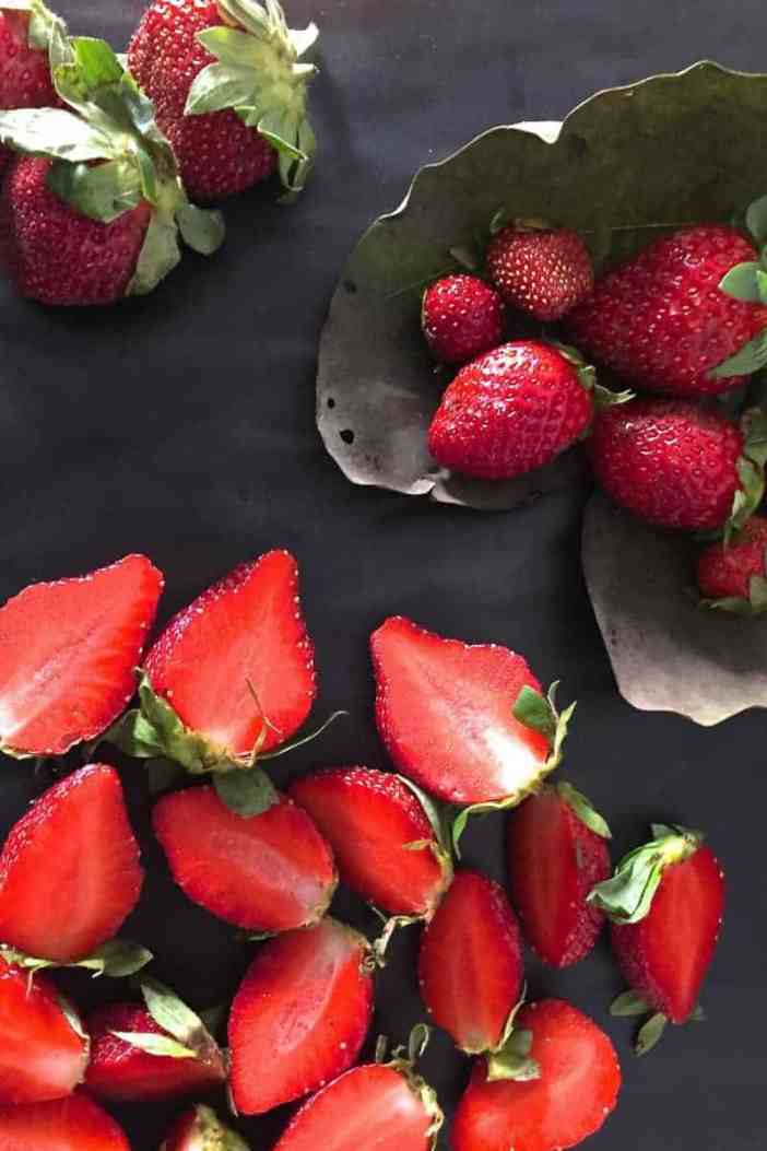 Bright red strawberries on a dried leaf and more strawberries on a black background