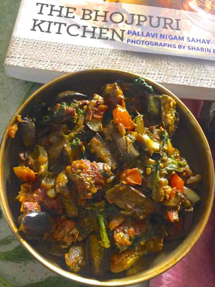 A round bowl filled with Baingan Badi Sabzi - sliced eggplant curry with homemade black gram dhal fritters and a part of a cookbook shown above it