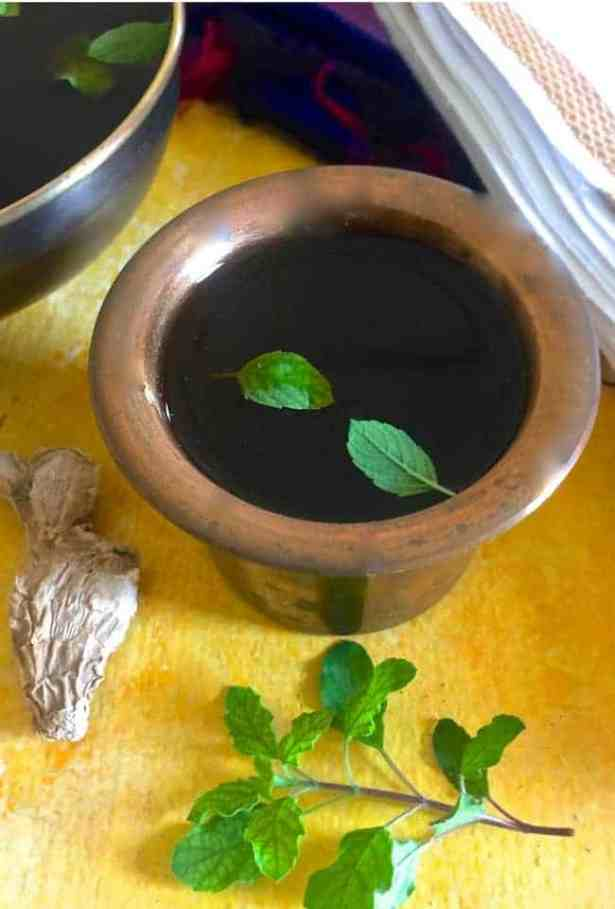 Brass tumbler with cooling dark jaggery drink Panakam with tulsi leaves as garnish, on a yellow background
