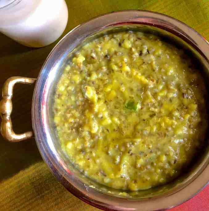 A brass bowl with an handle to the left filled with greenish brown Bajra Khichdi of Pearl millets and a glass of buttermilk by the side